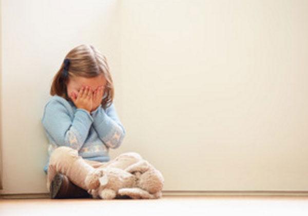 Девочка сидит под стенкой, прячет лицо руками