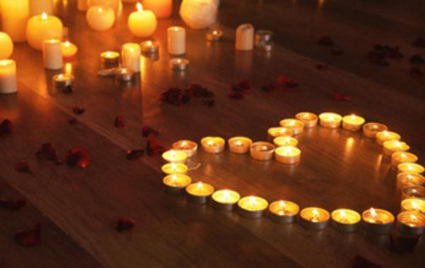 Сердце из зажженных свечей на полу. Рядом лепестки роз и другие свечи