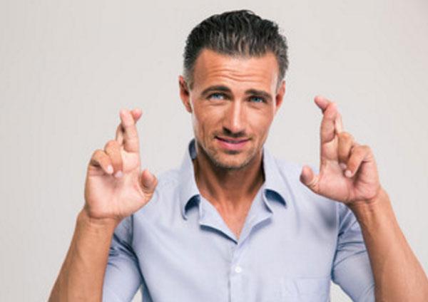 Сужчина со скрещенными пальцами на обеих руках