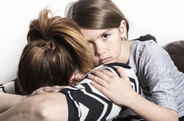 Женщина плачет на столе, дочка прижимается к ней, пытается ее успокоить