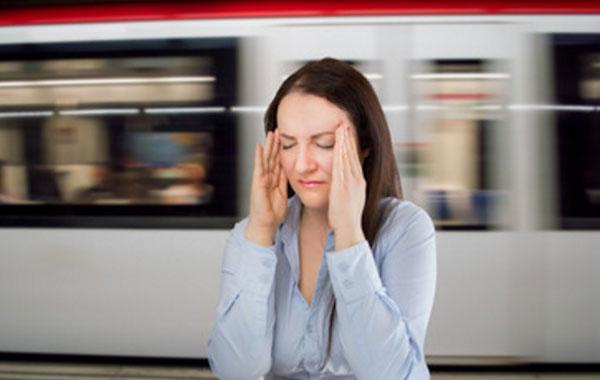 Женщина держит пальцы на висках. Сзади проносится вагон поезда в метро