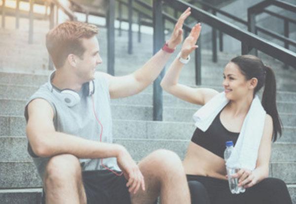Парень с девушкой в спортивной одежде {amp}quot;дают пять{amp}quot;, сидя на ступеньках