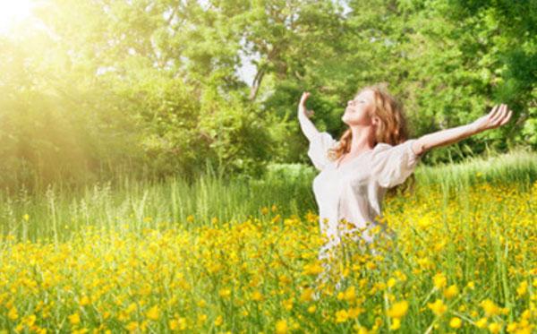 Женщина идет по поляне и радуется солнечным лучам