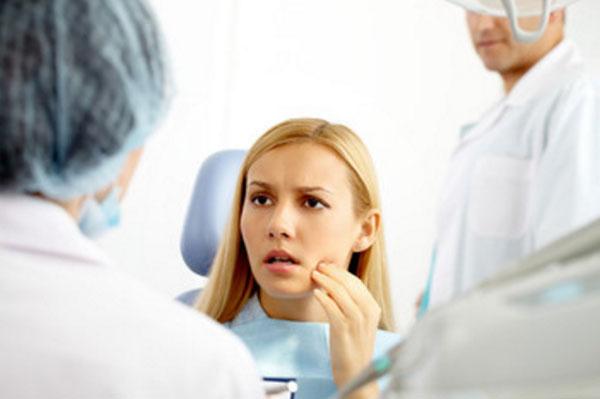 Девушка держится за зуб. Видно, что врач ее успокоил, уже не так страшно