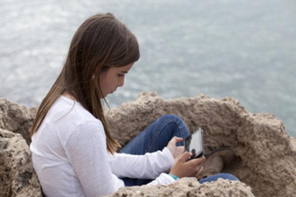 Девочка сидит на возвышенности возле моря с мобильником в руках