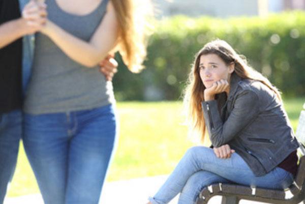 Девушка с завистью смотрит на проходящую мимо пару