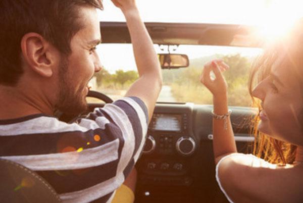 Парень с девушкой едут в машине. Вид с заднего сидения