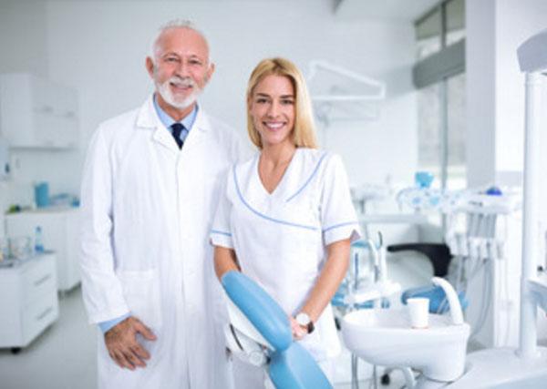Стоматологический кабинет. Стоят улыбающиеся врач и медсестра