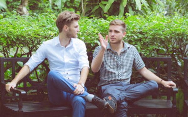 Мужчина что-то рассказывает и показывает другому мужчине, сидя на скамье