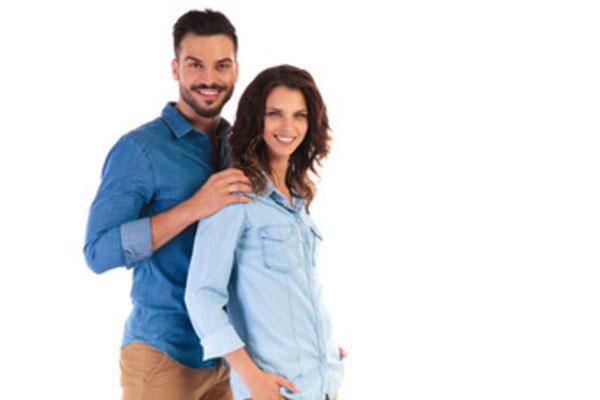 Мужчина стоит сзади женщины, обнимает ее за плечи