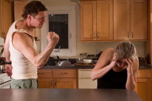Женщина сидит за столом, испугана, пытается спрятаться от удара. Мужчина угрожает ей кулаком