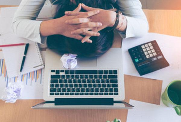 Женщина лежит лицом на столе. Рядом ноутбук, калькулятор, блокнот с ручкой