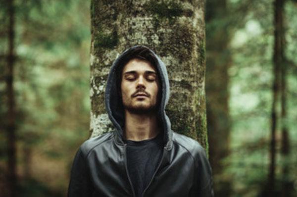 Одинокий мужчина стоит под деревом