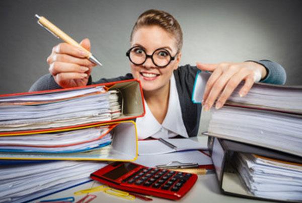 Женщина за столом, обложенная папками с бумагами