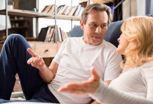 Муж с женой спокойно общаются на диване