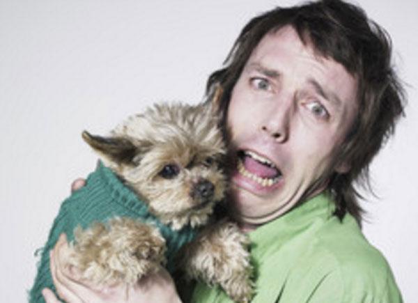 Мужчина с ужасом держит на руках маленькую собачку