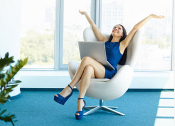 Счастливая женщина сидит на кресле, на коленях ноутбук