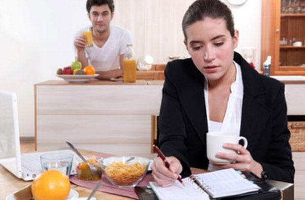 Женщина трудиться и пьет чай на ходу. На заднем плане мужчина пьет сок