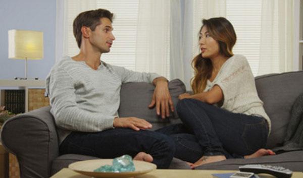 Жена с мужем разговаривают, сидя на диване