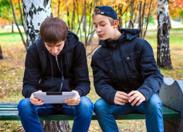 Мальчик смотрит на гаджет парня, сидящего рядом на скамейке