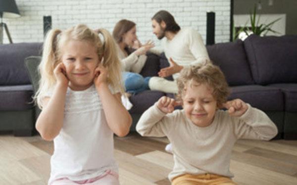 Дети сидят на полу, закрыв уши. На заднем плане родители ругаются, сидя на диване