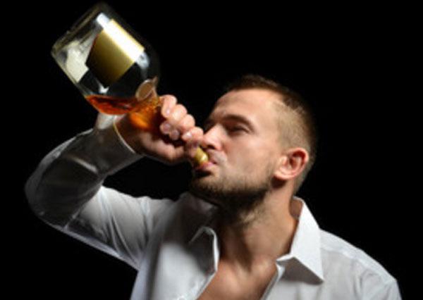 Мужчина с горла пьет спиртной напиток