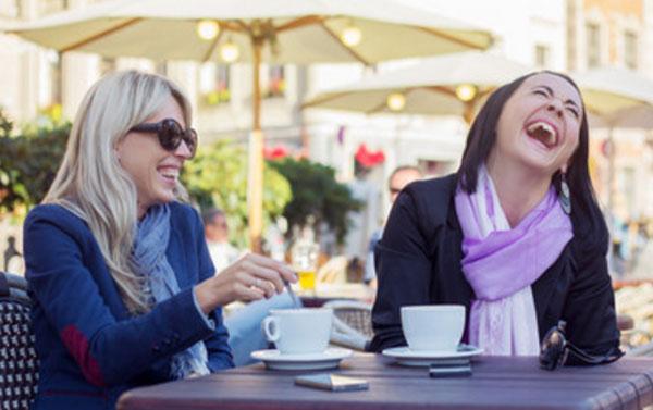 Женщины сидят в кафе и смеются