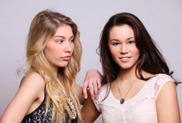 Две девушки стоят вместе, одна завистливо поглядывает