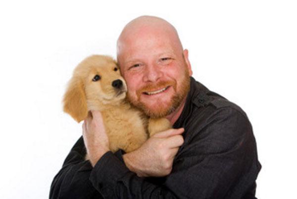 Счастливый мужчина обнимает щенка