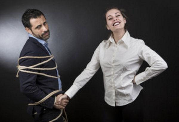 Женщина стоит рядом со связанным мужчиной