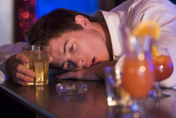 Пьяный мужчина с стаканом алкоголя в руках лежит на стойке бара