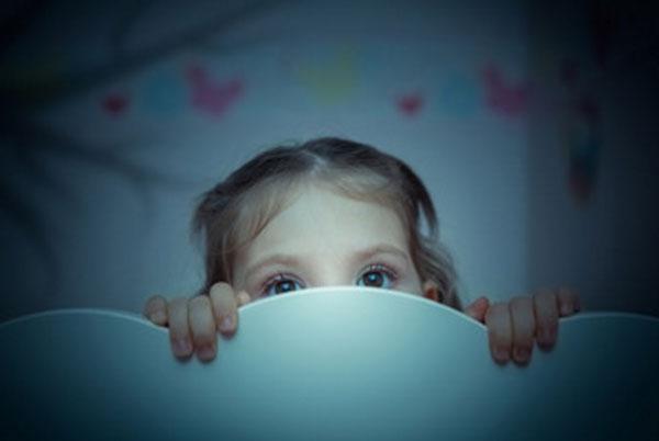 Девочка в темноте выглядывает из-за спинки кровати