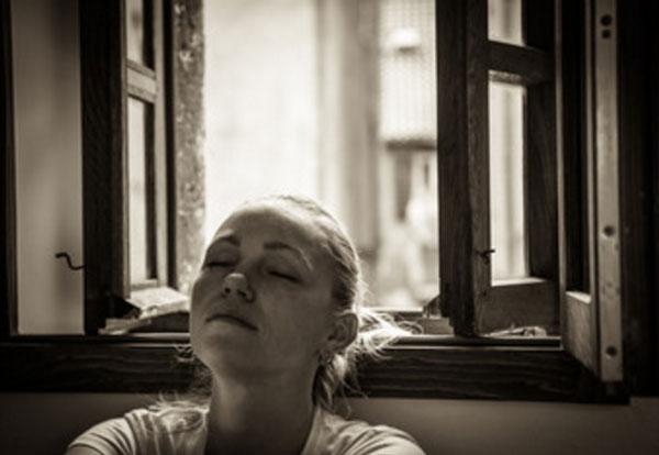 Грустная девушка с закрытыми глазами сидит у окна