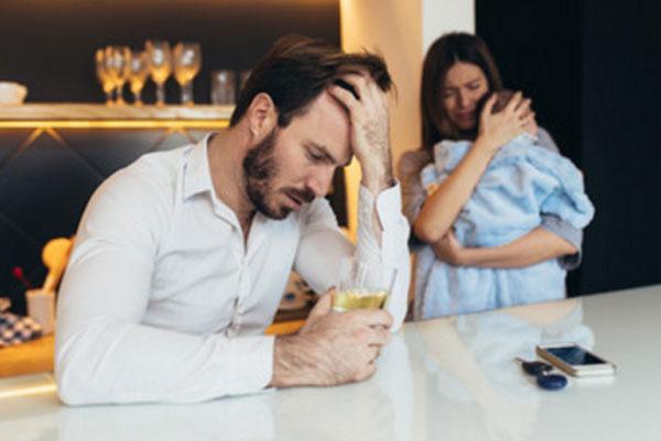 Женщина с грудничком на руках. Мужчина держит стакан с алкогольным напитком в руке и держится за голову