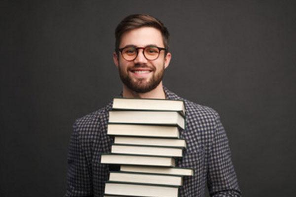 Улыбающийся парень в очках с стопкой книг в руках