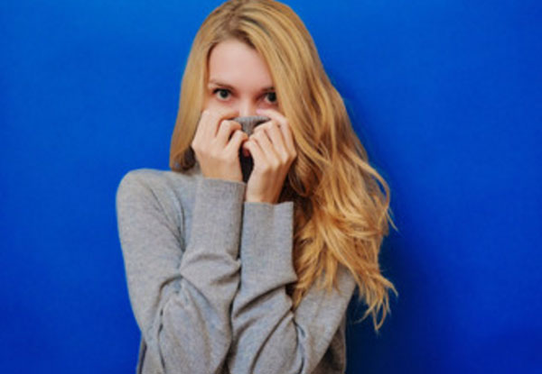 Девушка прячется в воротник свитера