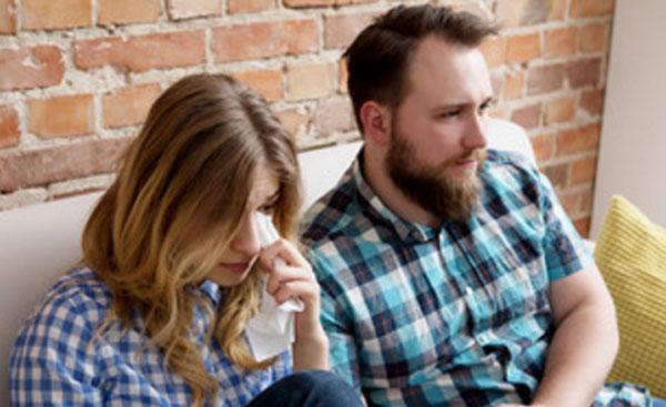 Девушка с парнем на диване. Она плачет, а он смотрит прямо