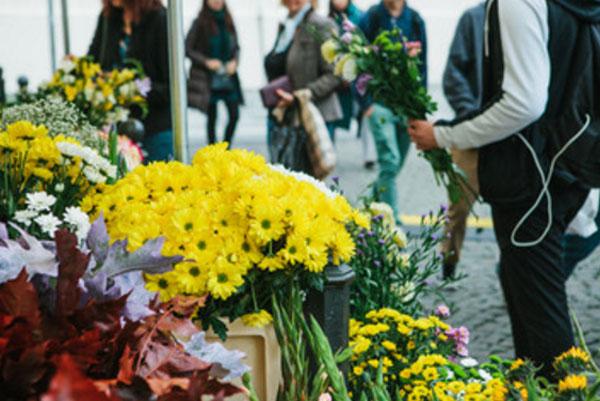 Парень стоит со скромным букетом в руке возле цветочного магазина