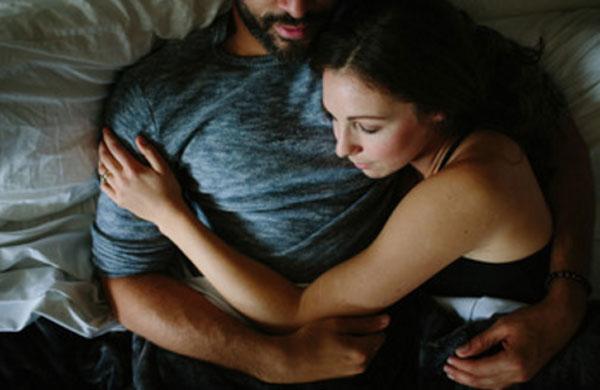 Девушка обнимает парня в постеле
