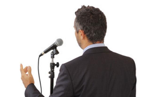 Вид ухоженного мужчины в костюме, который уверенно говорит перед микрофоном