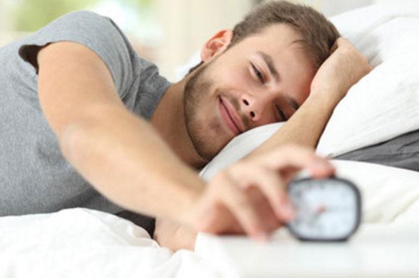 Улыбающийся мужчина нажимает на кнопку будильника