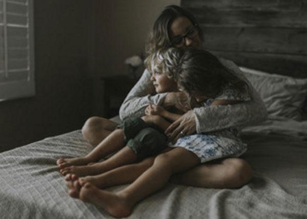 Женщина обнимает своих детей