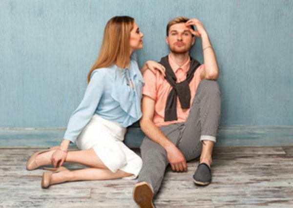 Девушка и парень сидят под стенкой. Он смотрит прямо, а она на него