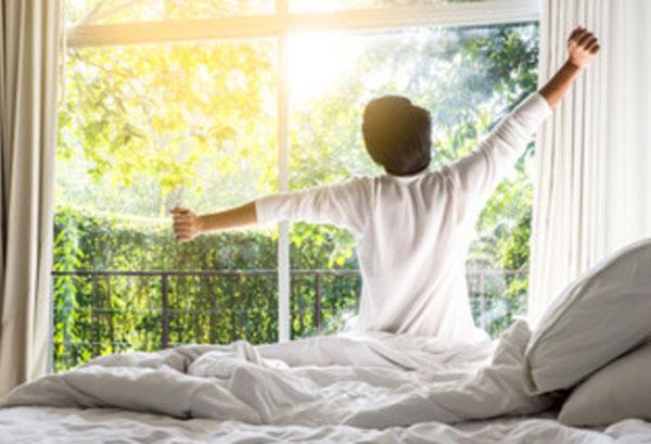 Мужчина проснулся, растягивается. За окном солнечное утро
