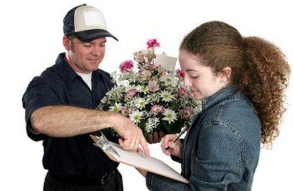Курьер передает цветы девушке