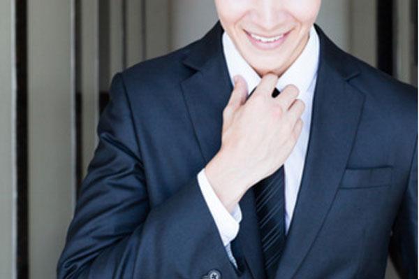 Улыбающийся парень поправляет галстук
