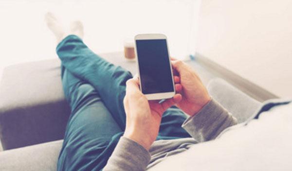 Парень сидит на диване и смотрит на темный экран мобильного телефона