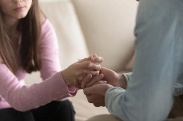 Парень держит девушку за руку