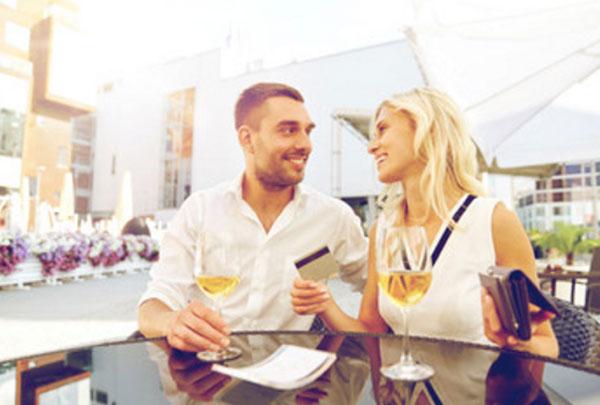 Мужчина с женщиной сидят в кафе с бокалами вина. Женщина достала из сумочки кредитку