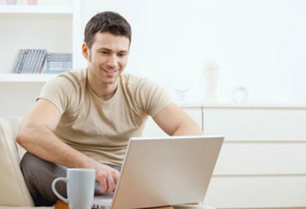 Мужчина пишет сообщения на ноутбуке и улыбается